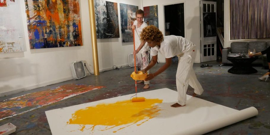 Two woman are painting with yellow color painting